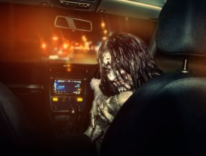 Zombie rides in a car at nighttime with a sinister grin